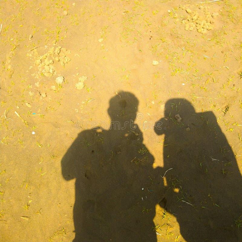 Een paar schaduwen op het zand royalty-vrije stock afbeeldingen