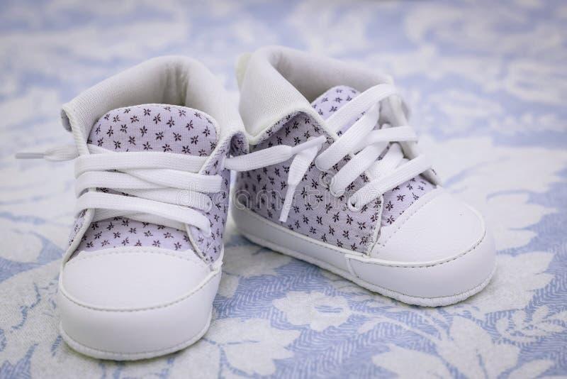 Een paar schoenen voor een jonge baby Purpere schoenen voor baby op de deken royalty-vrije stock foto