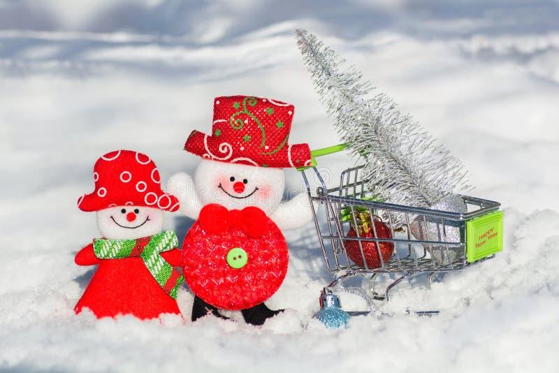 Een paar sneeuwmannen een echtgenoot en een vrouw in een kruidenierswinkelkar drijft een Kerstboom en een speelgoedhuis Vrolijke  stock fotografie
