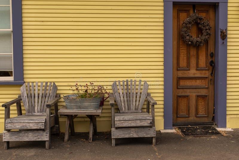 Een paar stoelen buiten de voorzijde van een geel geschilderd huis royalty-vrije stock foto's