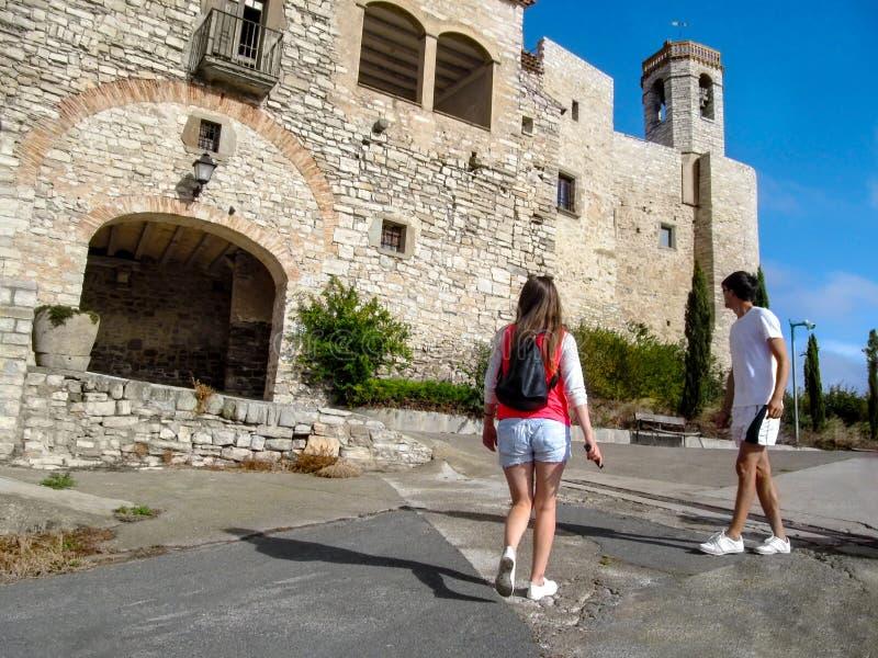 Een paar toeristen komen aan de muren van het kasteel Montfalco Murallat, La Segarra, Lleida provincie in Catalonië, Spanje nader royalty-vrije stock foto's