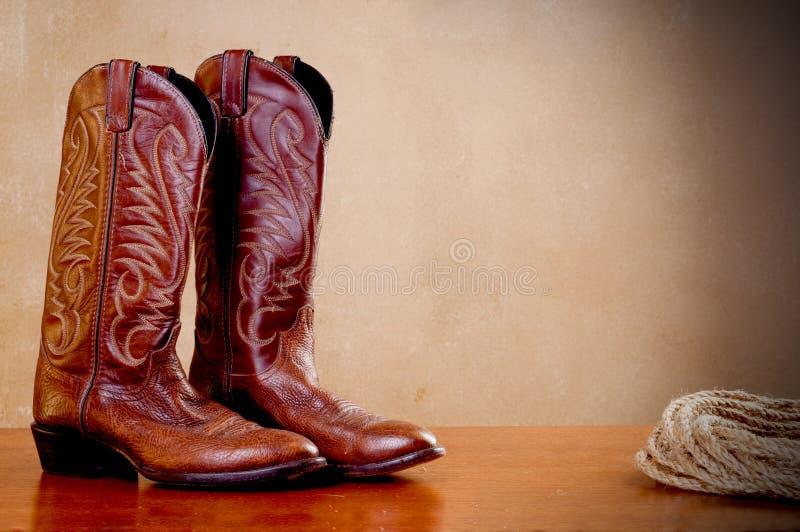 Een paar van bruine cowboylaarzen en een rol van kabel stock foto's