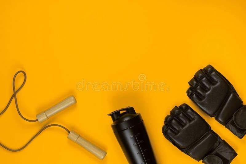 Een paar van het bestrijden van handschoenen naast een waterfles en een springtouw royalty-vrije stock fotografie