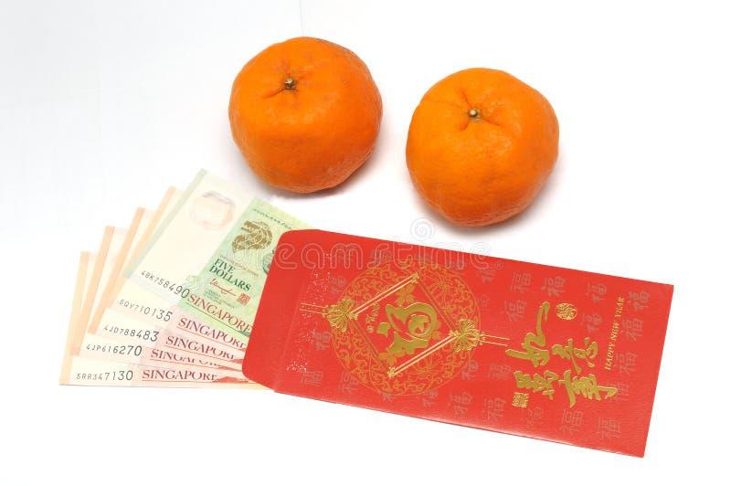 Een paar van mandarijntjes en een rode envelop met het geld binnen nota's van Singapore stock fotografie