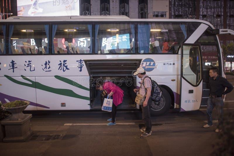 Een paar van toeristenpaar die op middelbare leeftijd van de bus terugkeren om hun bagage, nachtmening op te nemen stock foto