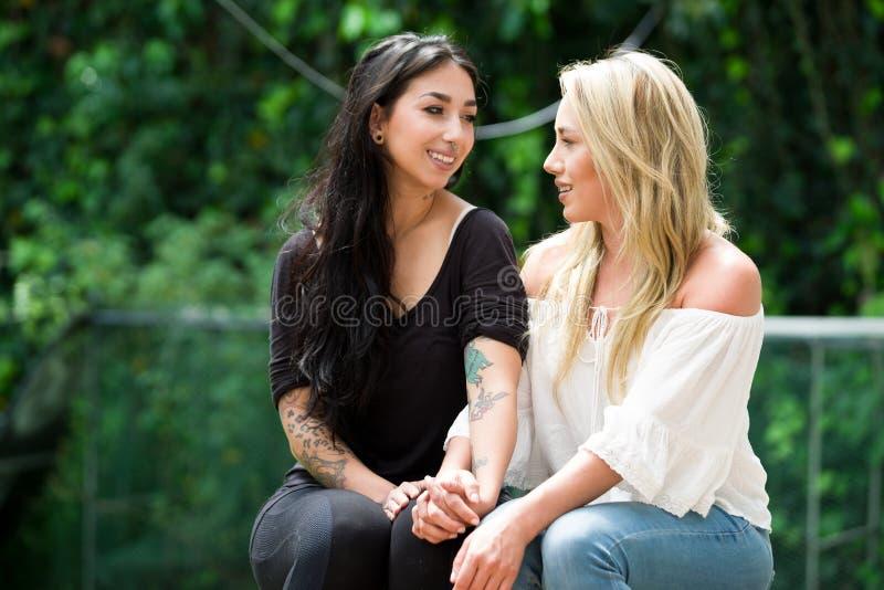 Een paar van trotse lesbienne in in openlucht het bekijken elkaar, op een tuinachtergrond royalty-vrije stock foto