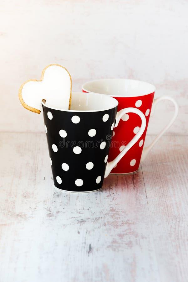 Een paar van zwarte en rode polka stippelde koffiekoppen met een hart gevormd eigengemaakt koekje op de rand over witte houten ac royalty-vrije stock afbeelding