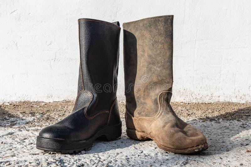 Een paar verschillende laarzen buiten Contrast oude en nieuwe, schone en vuile schoenen stock foto's