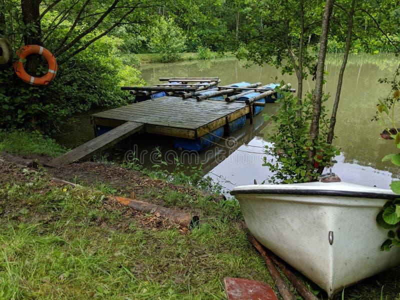 Een paar vlotten op een ponton met een kleine het roeien boot op de kustbank royalty-vrije stock afbeelding