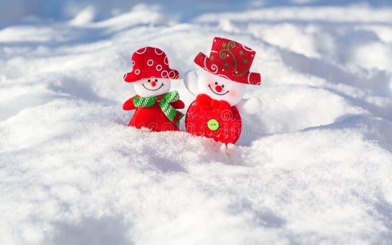 Een paar vrolijke sneeuwmannen in de sneeuw royalty-vrije stock fotografie