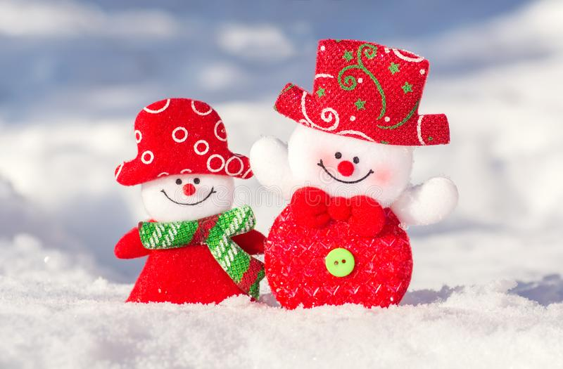 Een paar vrolijke sneeuwmannen in de sneeuw stock afbeelding