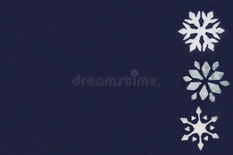 Een paar witte sneeuwvlokken zijn geschilderd door een stencil op een donkerblauwe achtergrond De ruimte van het exemplaar stock afbeelding