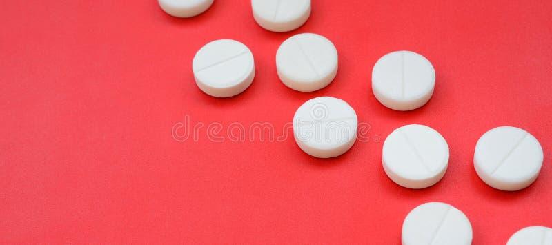 Een paar witte tabletten liggen op een heldere rode oppervlakte als achtergrond Achtergrond op medische en farmaceutische onderwe stock foto