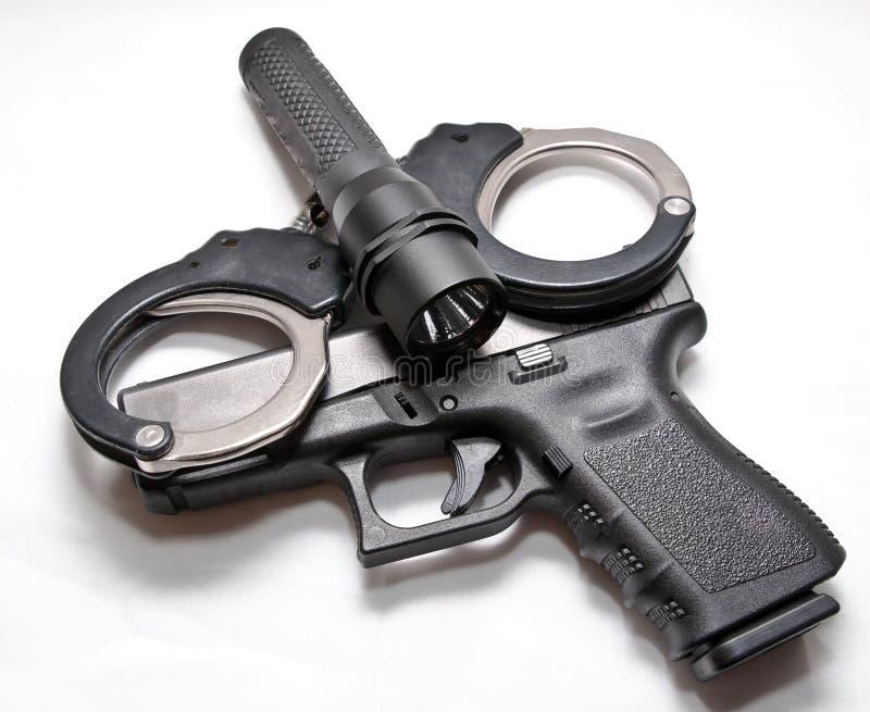Een paar zwarte en zilveren handcuffs met een zwart flitslicht die bovenop een zwart semi automatisch pistool leggen stock afbeeldingen