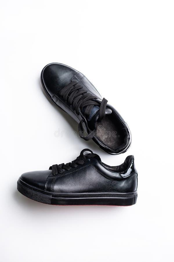 Een paar zwarte in tennisschoenen op de witte achtergrond royalty-vrije stock afbeelding
