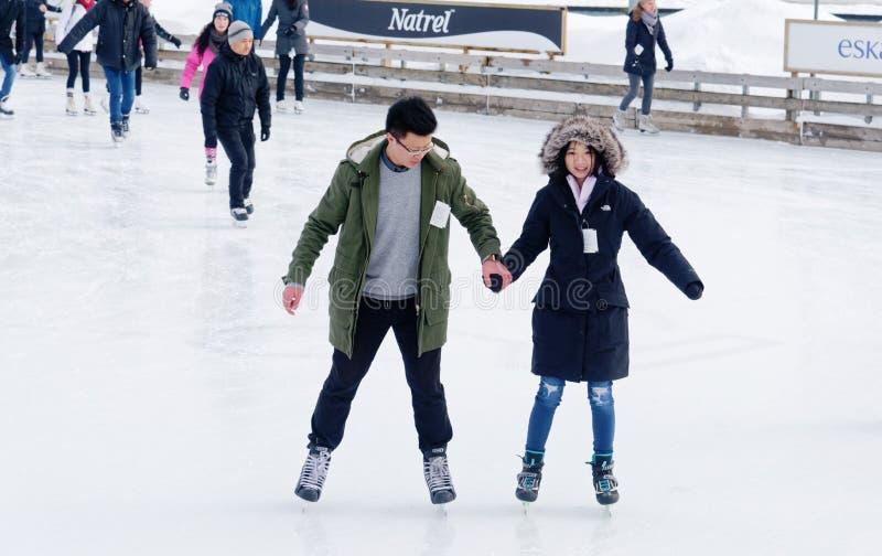 Een paarijs die op een openluchtpiste in Montreal schaatsen stock fotografie