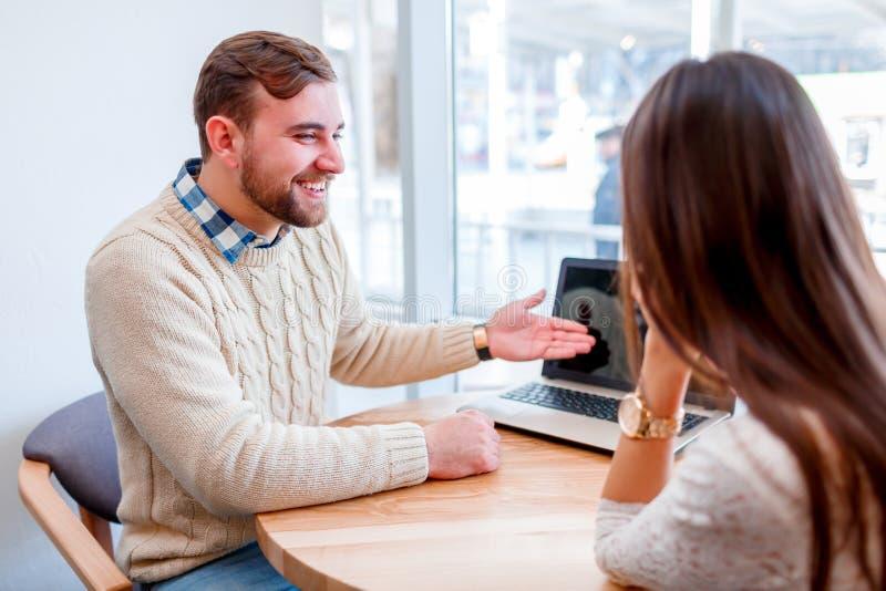 Een paarzitting in een koffie die, een kerel richt op laptop cheerfully lachen royalty-vrije stock afbeelding