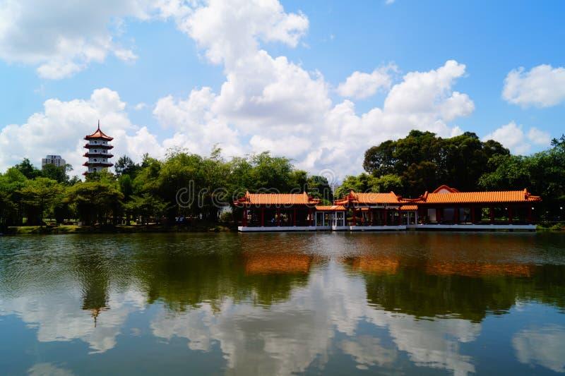 een pagode in het meer en een het voeden vissenhuis stock fotografie