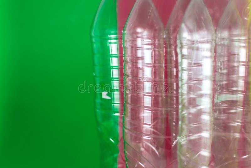 Een pak lege en rekupereerbare plastic waterflessen, op een gekleurde trillende groene en wijn rode achtergrond Hergebruik, Eco royalty-vrije stock afbeelding