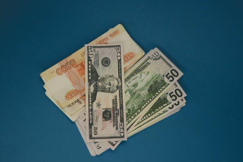 een pak Russische roebels en dollars twee pakjes van geld op een blauwe achtergrond rijkdom van kans Succes stock fotografie