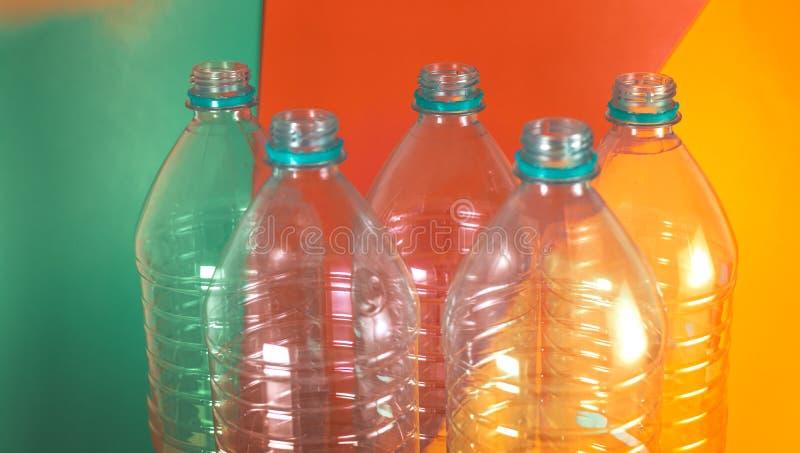 Een pak van 5 lege en rekupereerbare waterflessen, zonder kappen, op een gekleurde trillende achtergrond met groen, oranje overze stock foto's