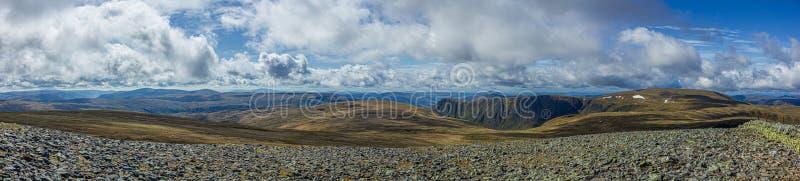 Een panoramamening van een Schots plateau van de bergtop met heide en klip onder een majestueuze blauwe hemel en reusachtige witt royalty-vrije stock fotografie