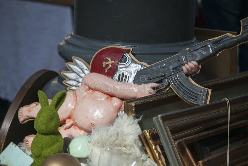 Een parodie van de Sovjetunie Plastic naakte engel in een gasmasker en een helm van een Sovjetmilitair met een Kalashnikovgeweer stock fotografie