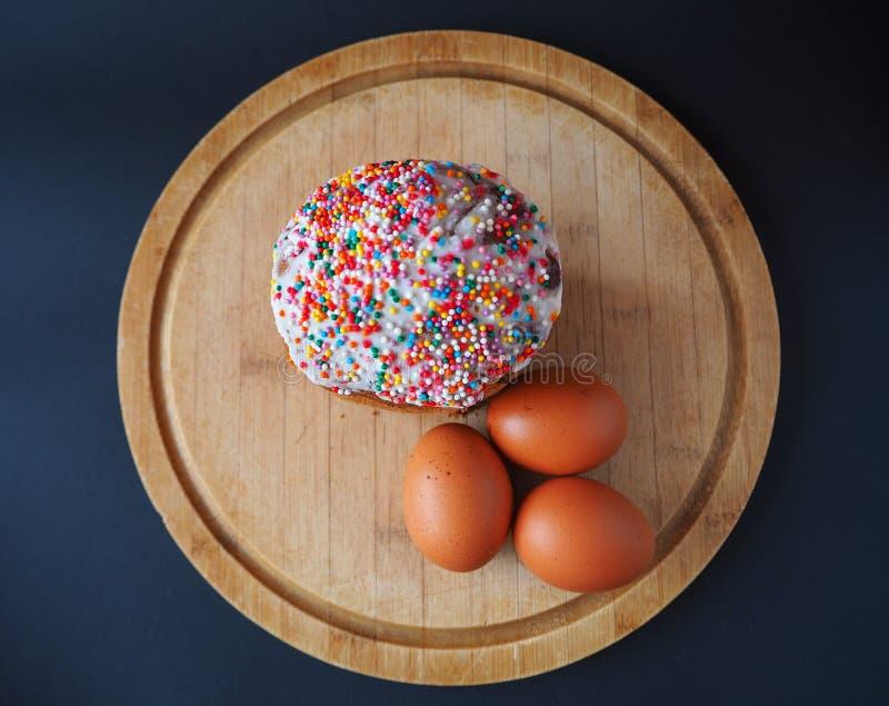 Een Pasen-cake met drie eieren op de houten raadsbovenkant stock fotografie