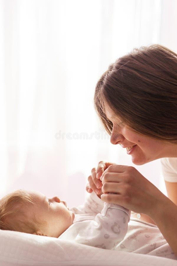 Een pasgeboren baby ligt op het bed en de moeder houdt zijn handen stock foto
