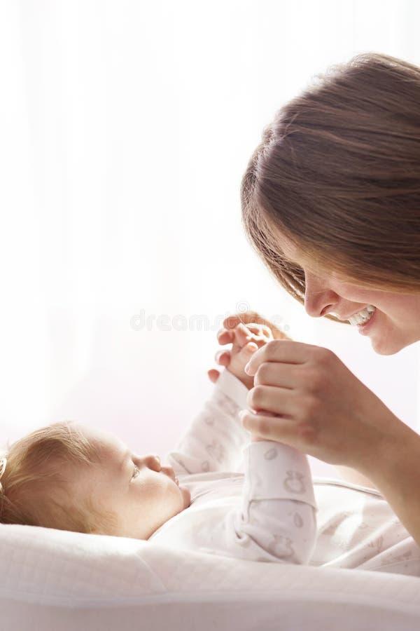 Een pasgeboren baby ligt op het bed en de moeder houdt zijn handen royalty-vrije stock afbeelding