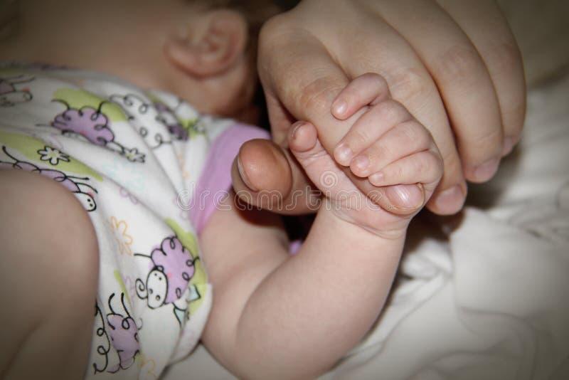 Een pasgeboren de ouder` s vinger van de baby` s hand holdind stock fotografie