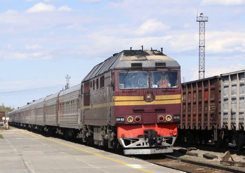 Een passagierstrein met een diesel locomotief nadert het platform van het station, de stad van Pyt ` - Yakh, Rusland royalty-vrije stock foto