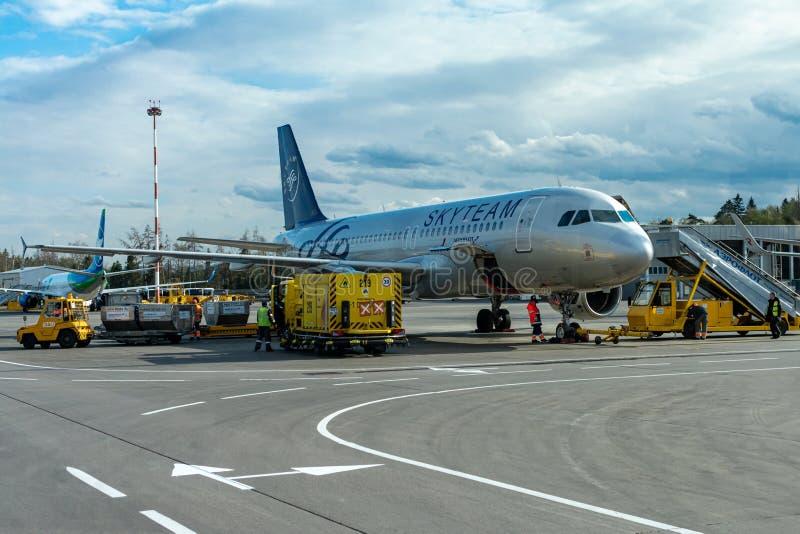 Een passagiersvliegtuig bevindt zich bij de luchthaven in een parkeerplaats die op vertrek, het proces wachten om voorbereidingen stock foto