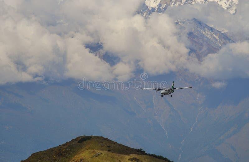 Een passagiersvliegtuig die over de bergen vliegen stock afbeelding