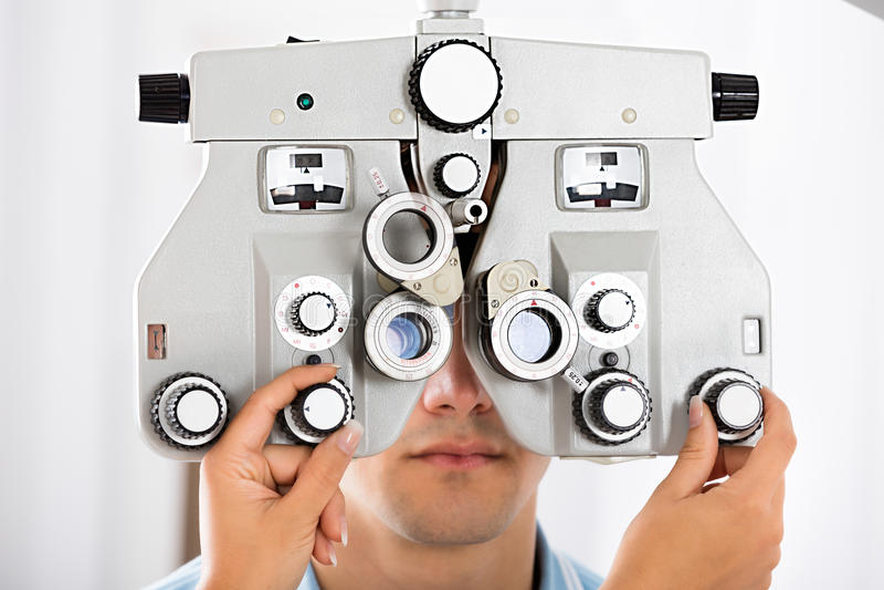 Een Patiënt van Optometristadjusting phoropter for royalty-vrije stock afbeeldingen