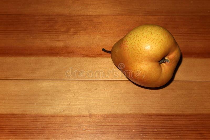 Een peer van gele kleur rust op een houten lijst royalty-vrije stock foto's