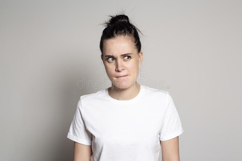 Een peinzende, betwijfelende jonge vrouw trok haar lippen samen en kijkt suspiciously aan de kant Op een witte achtergrond royalty-vrije stock foto