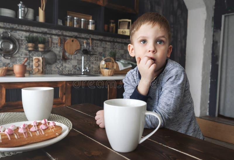 Een peinzende kleine jongen zit bij een lijst met een circleythee en cakes royalty-vrije stock afbeeldingen