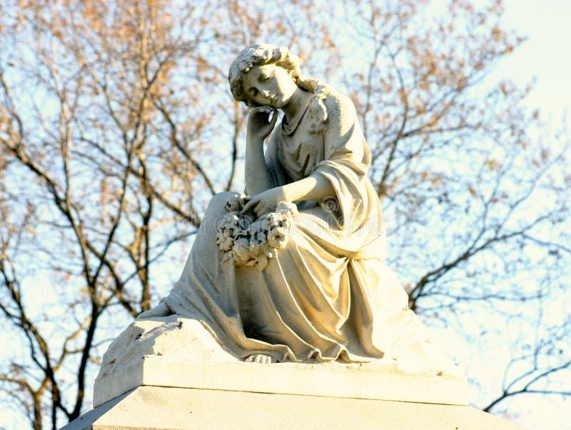 Een peinzende standbeeldzitting bovenop een grafsteen royalty-vrije stock afbeeldingen