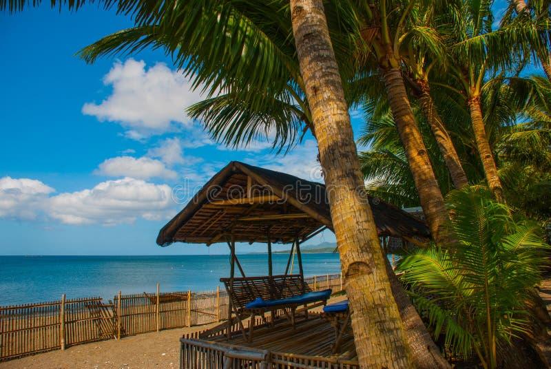 Een pergola van riet, de omheining op het vulkanische strand wordt gemaakt dat Pandan, Panay, Filippijnen stock foto's