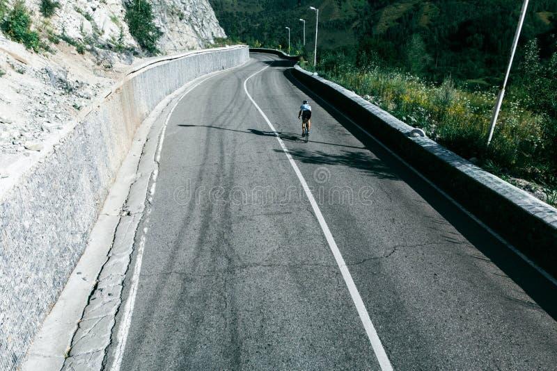 Een personenvervoer een fiets op een bergweg Lucht Mening stock afbeelding
