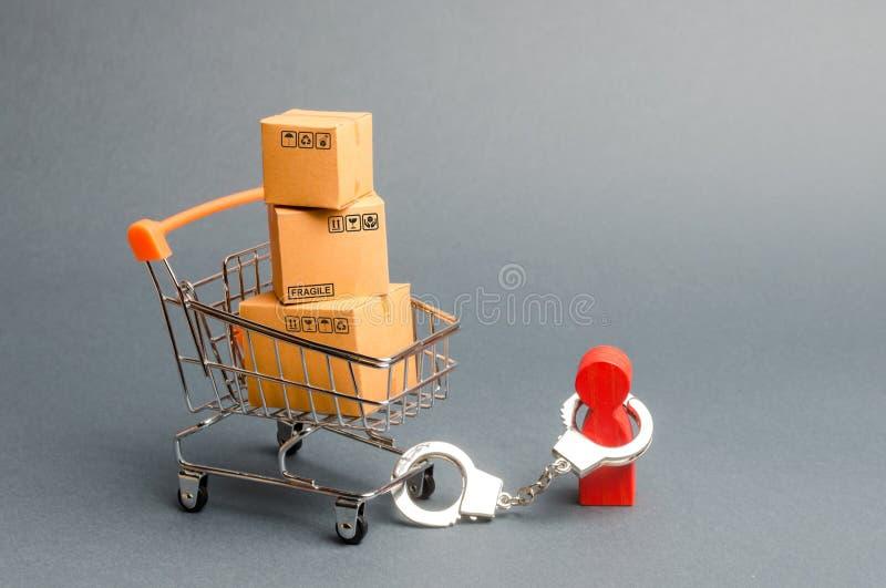 Een persoon de handboeien om:doen aan een bos van dozen a op een supermarktkar Het concept afhankelijkheid van het winkelen en he royalty-vrije stock fotografie