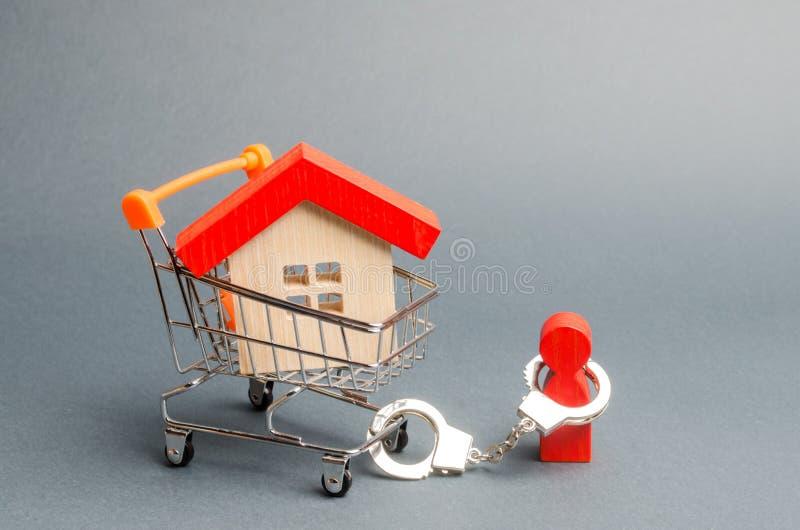 Een persoon de handboeien om:doen aan een huis op een supermarktkar Het concept een grote schuld op een lening of een hypotheek F stock foto