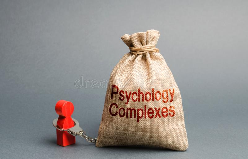Een persoon de handboeien om:doen met een zak ge?tiketteerd psychologische complexen Gevoel van minderwaardigheid en laag zelfres stock afbeeldingen