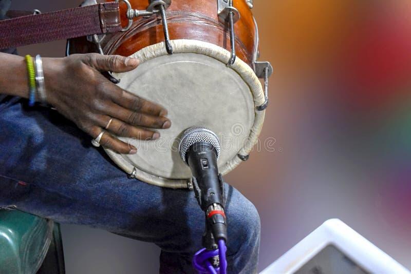 Een persoon die Dhole spelen, - Dhole/Dholoke is een muzikaal instrument dat door wordt geklonken door een klopper worden geslage royalty-vrije stock afbeeldingen
