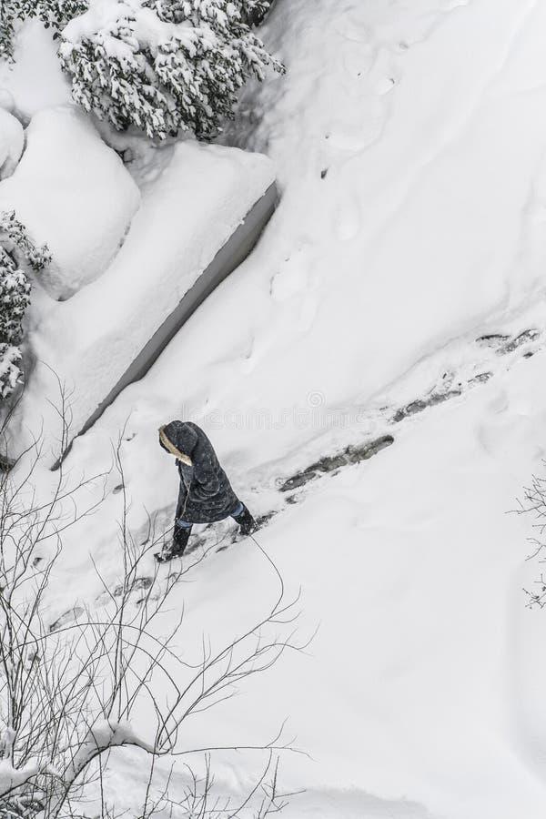 Een persoon die op sneeuw in de winter lopen stock foto's