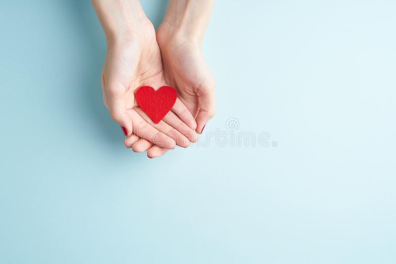 Een persoon die rood hart in handen, schenkt en het concept van de familieverzekering houden, op aquamarijnachtergrond, exemplaar royalty-vrije stock fotografie