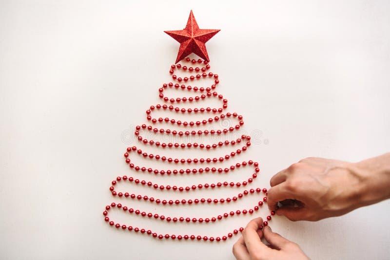 Een persoon maakt een creatieve die Kerstmis of Nieuwjaarboom van parels in een minimalistic stijl wordt gemaakt en verfraait met royalty-vrije stock foto