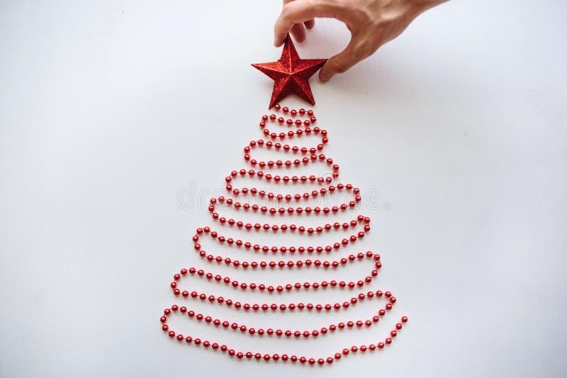 Een persoon maakt een creatieve die Kerstmis of Nieuwjaarboom van parels in een minimalistic stijl wordt gemaakt en verfraait met royalty-vrije stock afbeeldingen