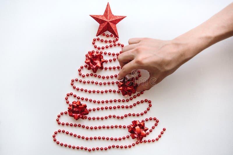 Een persoon maakt een creatieve die Kerstmis of Nieuwjaarboom van parels in een minimalistic stijl wordt gemaakt en verfraait met stock afbeeldingen